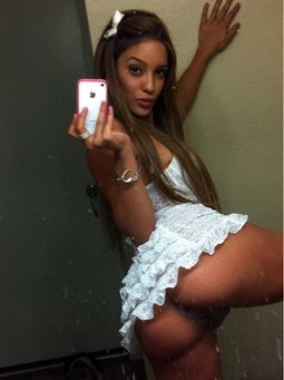 Sexy brunette latina taking selfshot in white lingerie.